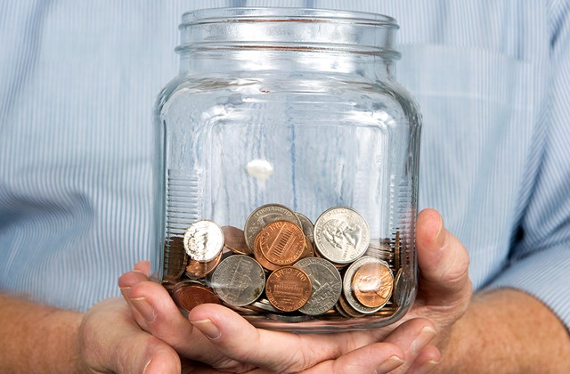 mans-hands-holding-third-full-jar-of-coins-mst