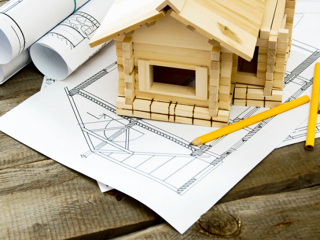 Many drawings for building and small house on old wooden backgro
